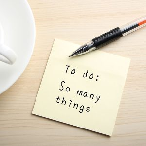 A yellow sticky note is written something on the desk with a cup of coffee and a ball pen aside.