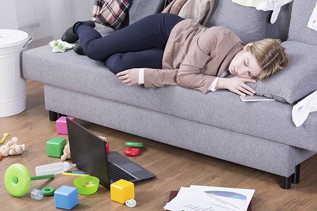 Young mother sleeping in her office clothes on a sofa in a messy living room
