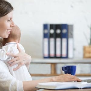 Side view portrait of happy casual young business mom holding her newborn cute babe while working on laptop in home office interior. Smiling working mother using pc computer and nursing new born child