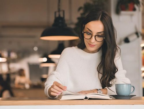 Attractive young woman in eyeglasses reading book at table with coffee cup in cafe