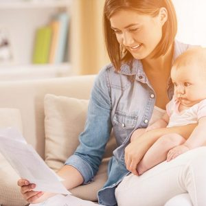 Young Woman with Baby Working at Home with Laptop. Single Mother. Parenthood Concept. Female Freelancer with Child. Girl with Digital Device. Sitting on White Sofa. Working Woman Concept.